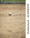Small photo of Low angle shallow depth of field round metal shot put ball laying on wet sand grains after impact at throwing competition in amateur youth track and field event