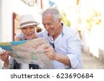 Senior couple of tourists looking at city map