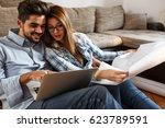 young couple examining... | Shutterstock . vector #623789591