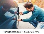 man changing wheel after a car... | Shutterstock . vector #623793791