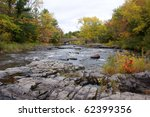 Photograph of the rapids of a northern wisconsin river taken during the beauty of the fall season.