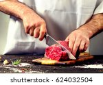 man cutting raw beef meat. | Shutterstock . vector #624032504