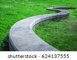 Small photo of A solid gray concrete serpentine park bench lying on a lawn of lush green grasses and accented by small white daisy flowers in Larkspur northern California.