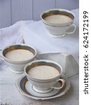 """Small photo of White dessert """"Junket"""" from milk and rennet extract with cinnamon in cups on light background. Jelly-like pudding made from sweet cottage cheese. Healthy food. Space for text"""