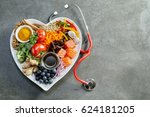 Small photo of Fresh food for a healthy heart with acai, lentils, soy sauce, ginger, salmon, carrot, tomato, turmeric, cinnamon, walnuts, garlic, peppers, broccoli, basil, onion with a stethoscope and copy space