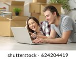 Small photo of Happy casual couple moving house searching information on line in a pc lying on the floor with boxes in the background