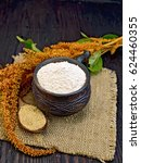 Small photo of Flour amaranth in a clay cup, a spoon with grain, brown flower with green leaves on a napkin from a sacking on a background of wooden boards