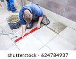Tiling Floor & Wall. The tiler builder arranges the bathroom ceramics. - stock photo