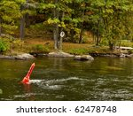 Red buoy in a fast river - stock photo