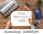 Small photo of The girl sits at the table with a mobile phone, a laptop, business accessories and a sheet with text Your text