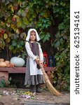Small photo of Cinderella cries in an old, dirty, torn dress, she is tired. Sweeps the floor off the bench. Preschool girl in the costume of Cinderella from the fairy tale by Charles Perrault. Emotional portrait