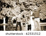 Small photo of Portrait of a fun young family with four children jumping in the air all at once. Sepia tone.