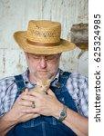 A Farmer Tenderly Holds A New...