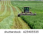 Small photo of Swan Valley, Idaho, USA July 1, 2013 A farmer, cutting and wind rowing alfalfa hay for drying, in the fertile farm fields of Idaho.
