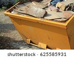 Small photo of Close up of a yellow skip with rubbish and construction waste