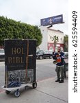 "Small photo of LOS ANGELES, FEB 26TH, 2017: A religious protester in a ""Trust Jesus"" shirt stands next to a giant bible replica as limousines go by on their way to the red carpet area at the 89th Academy Awards."