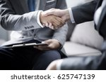 Small photo of businessman shaking hands to seal a deal with his partner