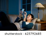 Small photo of college student using phone chatting online with classmate lying down on the living room sofa all-night usually, finally become habit unhealthy for human.