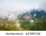 clouds over the forest in the mountains - stock photo