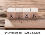 Small photo of Risk Word On Blocks Arranged Behind The Ruler On Wooden Table