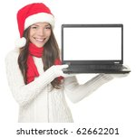 Laptop christmas girl. Smiling young woman in santa hat and sweater showing laptop. Copy space on computer screen. Caucasian Asian female model isolated on white background. - stock photo
