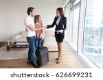 Small photo of Cheerful couple from another city country searching apartment for rent, shaking hands with female broker, travelers with travel bag suitcase looking for short-term accommodation, moving in new home