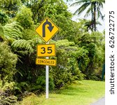 Small photo of Bright yellow advisory speed limit traffic sign, sharp bend to the right ahead traffic sign and concealed traffic sign with lush green background in the countryside, North Island, New Zealand