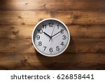 Wall Clock At Wooden Backgroun...