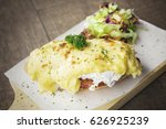 Small photo of Delicious egg benedict and salad above board on the wooden background