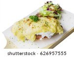 Small photo of Delicious egg benedict and salad on bake paper above board, isolated on white background