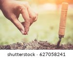 hand planting a seed in soil | Shutterstock . vector #627058241