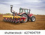 Small photo of Agriculture. Tractor in the field seeding and cultivating. Agronomy, husbandry concept.