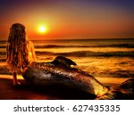 Small photo of Water nymph mermaid woman dreams on sea sandy beach. Fairy nixie girl looks at tropical setting sun. Fantasy sunset painted undine, sky and sea waves in gold. Magical fish tail of naiad shining squama