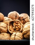 Small photo of Walnuts. Nuts of walnuts. Nuts in black plates against the background of a black wooden background. Rustic. Fresh autumn walnut harvest in the village. Place for text