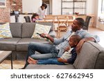 father and son sit on sofa in... | Shutterstock . vector #627662945
