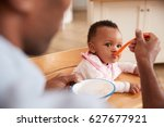 father feeding baby daughter in ... | Shutterstock . vector #627677921