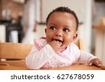 Stock photo cute baby girl wearing bib sitting in high chair 627678059