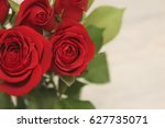 Stock photo red roses with green leaves on light grey background 627735071