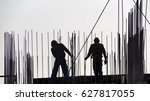 Two Builders In Helmets On The...