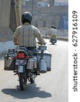 Small photo of JAIPUR, RAJASTHAN, INDIA - FEBRUARY 23, 2006: Man carrying milk, on a motorcycle, on the access road to the city