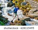 Female Hiker Crossing A Small...