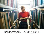 woman reading a book in library.... | Shutterstock . vector #628144511