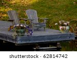 Two wooden Muskoka chairs on a dock - stock photo