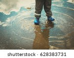 Little Boy In Rain Boots Play...