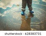 Little Boy In Rain Boots Play...