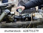 Small photo of The auto mechanic pours the engine oil additive in motor of old automobile