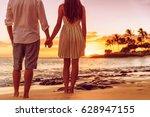 beach couple watching sunset... | Shutterstock . vector #628947155