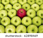 Small photo of red apple standing out from large group of green apples. Horizontal shape