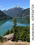 View of Diablo Lake and Mountains in the North Cascades National Park, Washington State in Bright Color with Trees and Rock in Forefront