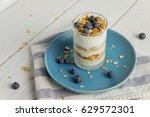 a glass of granola yogurt... | Shutterstock . vector #629572301